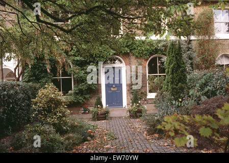 Shrubs growing in paved front garden on either side of path to blue front door of Victorian terraced townhouse - Stock Photo