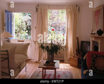 White curtains on window in nineties living room with white cushions on metal sofa - Stock Photo