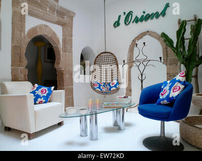 Bright Blue Cushions On White And Armchairs In Modern Moroccan Living Room With Glass Table