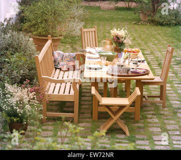 wooden chairs at table set for lunch on sunlit patio in country