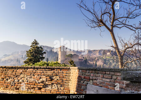 The brick walls of a medieval fortress and a sanctuary with steeple devoted to Blessed Virgin Mary on misty hills - Stock Photo