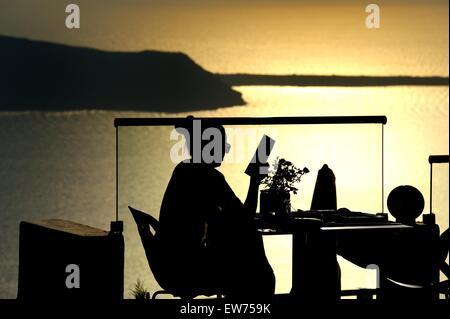 A lone female sitting at a sea view restaurant table in silhouette with the sun setting over the caldera, Imerovigli,Santorini. - Stock Photo