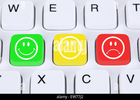 Choosing customer service quality feedback with smiley on computer keyboard - Stock Photo