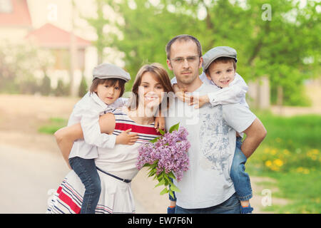 Family of four, mother, father and two boys, parent having the kids on piggy back, laughing, smiling, hugging, giving - Stock Photo