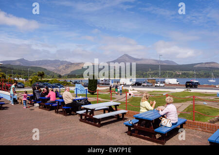 People sitting outside Little Rock cafe with a view to Goat Fell mountain across Brodick Bay on a sunny day. Brodick - Stock Photo