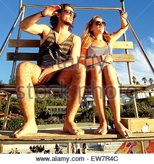 Man and woman sitting on a lifeguard tower, Clifton Beach, Cape Town, South Africa - Stock Photo