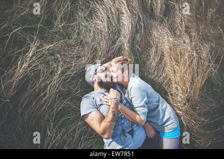 Elevated view of a couple lying on the grass - Stock Photo