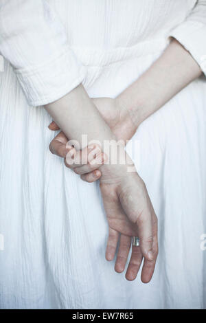 Rear view of woman holding hands behind her back - Stock Photo