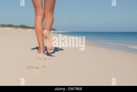 Close up of girl's legs walking on the beach - Stock Photo