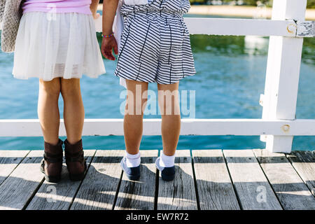 Low section of two girls standing on a jetty looking out to sea, Balmoral beach, Sydney, New South Wales, Australia - Stock Photo