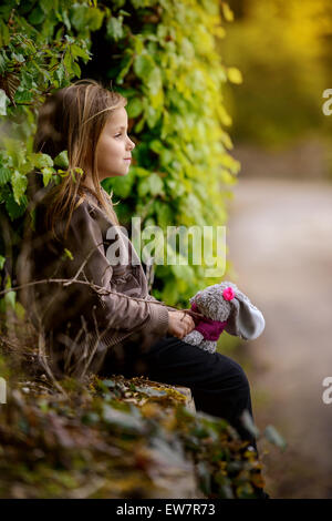 Side view of  a girl holding a stuffed bunny toy - Stock Photo
