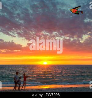 Three children flying a kite on beach at sunset, Hillarys, Joondalup, Australia - Stock Photo