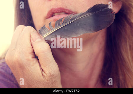 Close up of a woman holding a feather close to her face