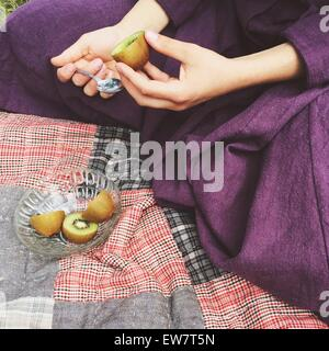 Close-up of a woman eating a kiwi fruit - Stock Photo