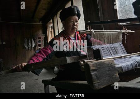 Chinese woman weaving fabric, Longsheng Village, Guilin, China - Stock Photo