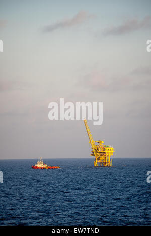 Supply ship leaving an oil and natural gas platform - Stock Photo