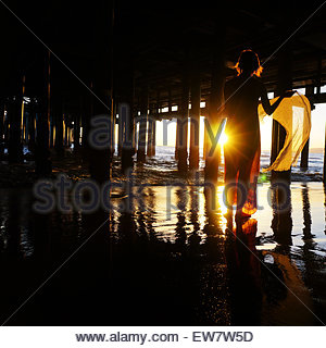 Silhouette of a woman standing under a pier - Stock Photo