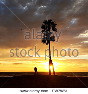 Silhouette of a couple standing on the beach at sunset, Playa del Ray, Los Angeles, LA, California, USA - Stock Photo