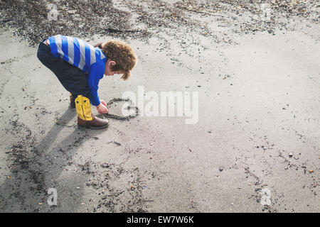 Boy in cowboy boots and raccoon hat drawing a heart in the sand - Stock Photo
