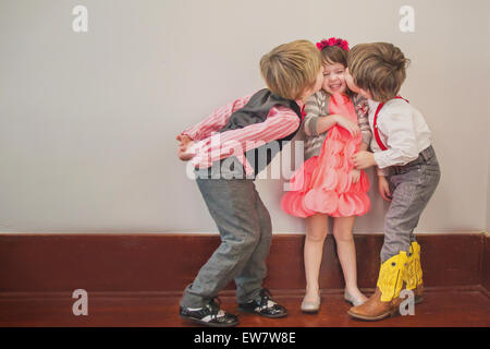 Two boys kissing a girl on the cheek - Stock Photo