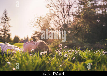 Boy laying in a field of flowers looking up at the sky - Stock Photo