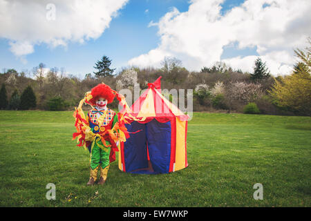 Boy dressed as a clown standing in front of a toy circus tent - Stock Photo