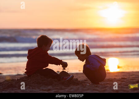 Two adorable kids, playing on the beach with sand on sunset - Stock Photo