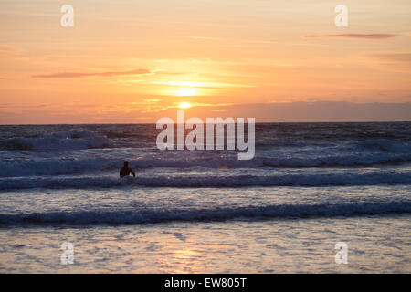 Surfer on the ocean beach at sunset - Stock Photo