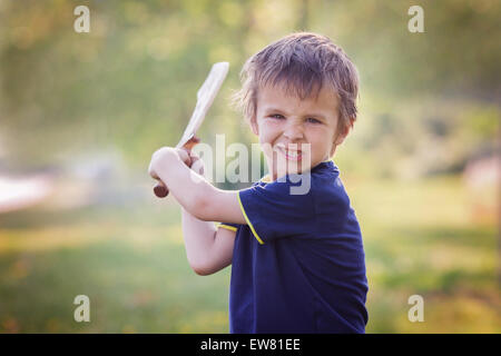 Angry little boy, holding sword, glaring with a mad face at the camera, outdoors in the park - Stock Photo