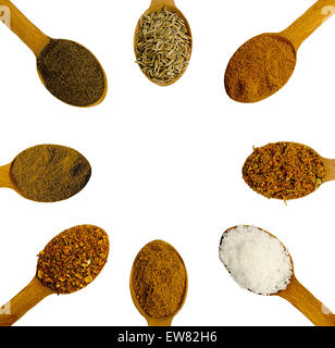 wooden spoons with spices with different spices on a white background - Stock Photo