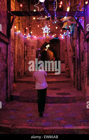 Israel, Jerusalem. 19th June, 2015. Young boy walking with Shisha pipe in an alley in the Muslim Quarter with festive - Stock Photo