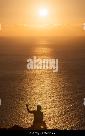 Woman taking a selfie near Lighthouse in Ponta do Pargo at sunset, Madeira island, Portugal - Stock Photo
