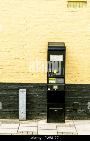Prepaid Parking meter installed against a painted brick wall in town centre, England - Stock Photo