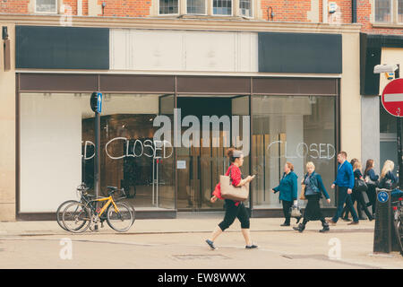 CAMBRIDGE, ENGLAND - 7 MAY 2015: 'Closed' Shop sign with shoppers walking past it, conceptual image of recession. - Stock Photo
