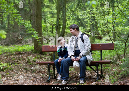 Father and son relaxing on a bench after a hike in the woods - Stock Photo