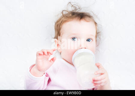 Little baby girl drinking milk out of a bottle - Stock Photo