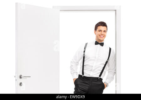 Handsome young man in elegant clothes posing by an opened door isolated on white background - Stock Photo