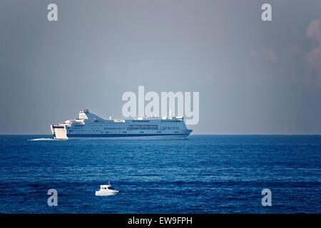 Ferry in the mediterranean sea and small civil boat near the Barcelona