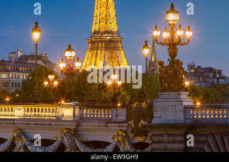 Twilight over lights of Pont Alexandre III with Eiffel Tower beyond, Paris, Ile-de-France, France - Stock Photo