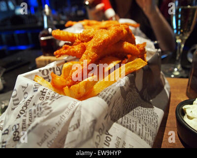 lemon sole goujons with chips on newspaper - Stock Photo