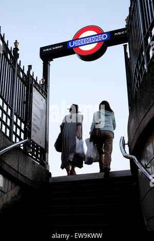 A rear view of two women leaving Charring Cross station, London - Stock Photo