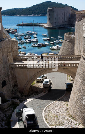 tourists on stone bridge to ploce gate entrance to old city and harbour of dubrovnik, croatia - Stock Photo