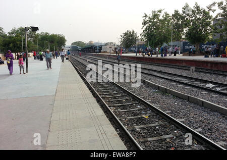 Gurgaon, India; 19th Jun'15: Passengers wiating at the Gurgaon (delhi NCR) railway station. The board is clearly - Stock Photo