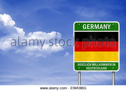 Welcome in Germany - road sign with German flag - Stock Photo