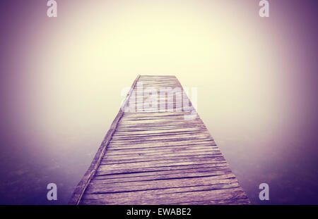Vintage filtered picture of old wooden pier in dense fog with strong vignette effect. - Stock Photo
