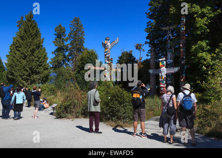 Visitors viewing and capturing images of the totem pole display at Brockton Point in Stanley Park  - Vancouver, - Stock Photo