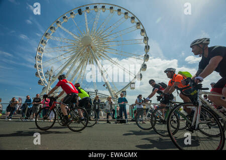 Brighton, UK. 21st June, 2015. Cyclists pass in front of Brighton Wheel on Madeira Drive. Onlookers stand at the - Stock Photo