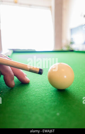 Bridging the pool cue on pool table - Stock Photo