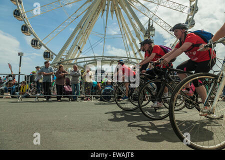 Brighton, UK, 21st June, 2015. Cyclists pass in front of Brighton Wheel. Onlookers watch behind barriers. Credit: - Stock Photo