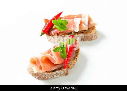 Prosciutto open faced sandwiches garnished with red chili peppers - Stock Photo